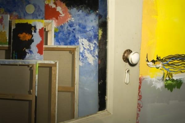 A porta do atelier de Guilherme Parente em Lisboa onde vemos arrumadas diferentes telas com pinturas em tons de vermelho e azul