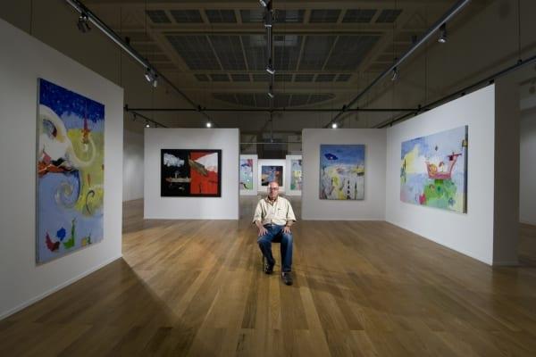 Guilherme Parente sentado no centro da sua exposição na Sociedade de Belas Artes em Lisboa