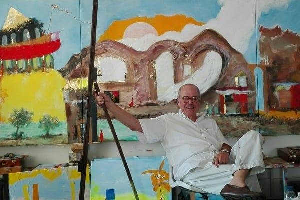 Guilherme Parente sentado no seu atelier em Lisboa rodeado pelos seus quadros em tons de azul, rosa e laranja